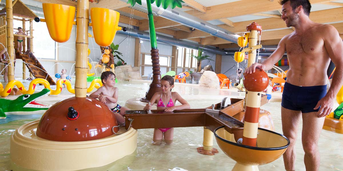A father and his children in the play area of the water park at Le Fief campsite